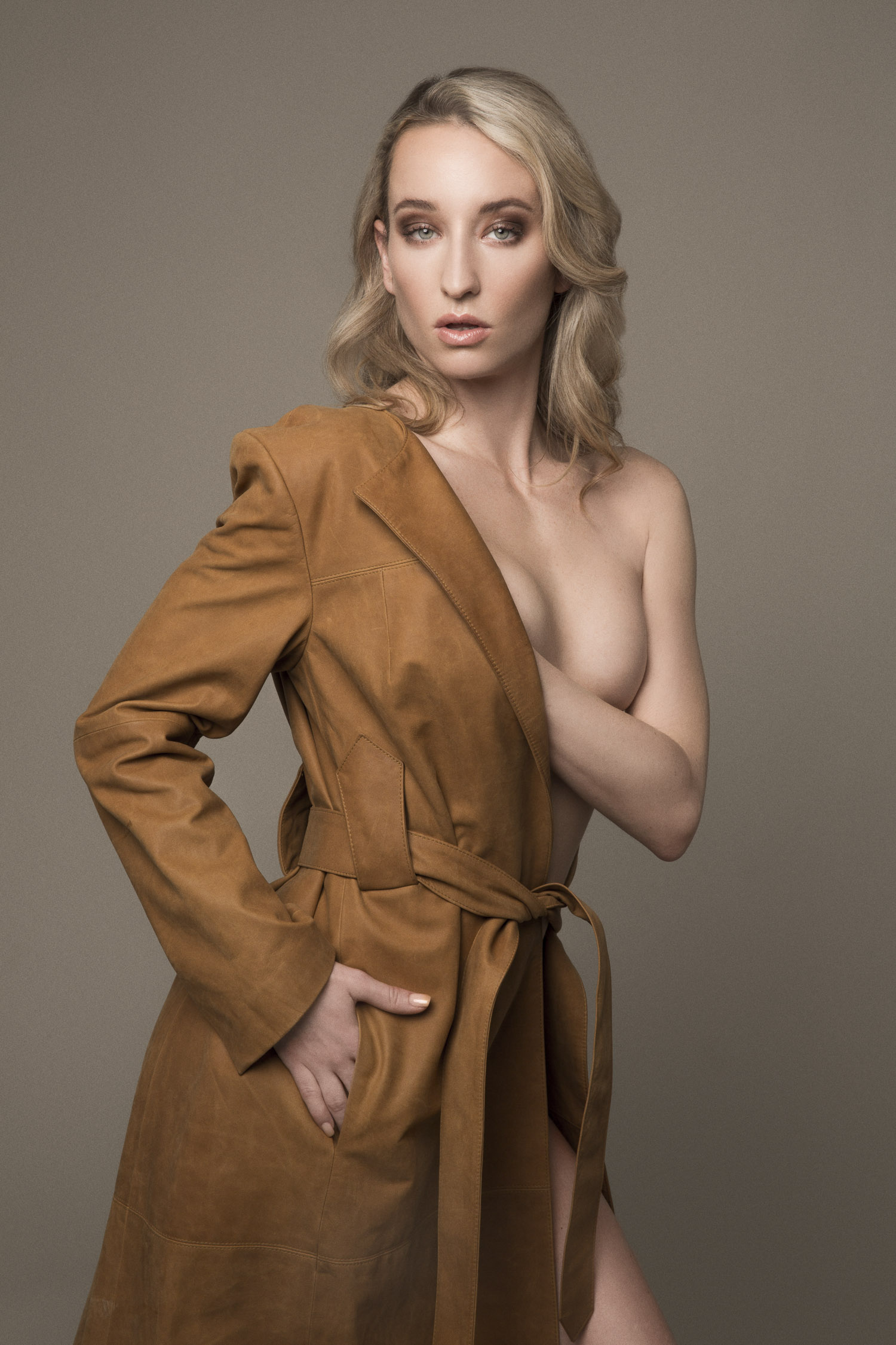 Model nude under a leather trenchcoat