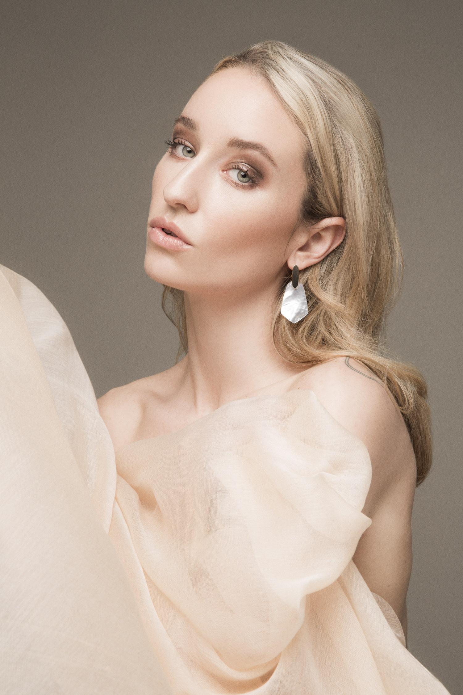 Beauty portrait of a blonde woman wearing Kendra Scott earrings