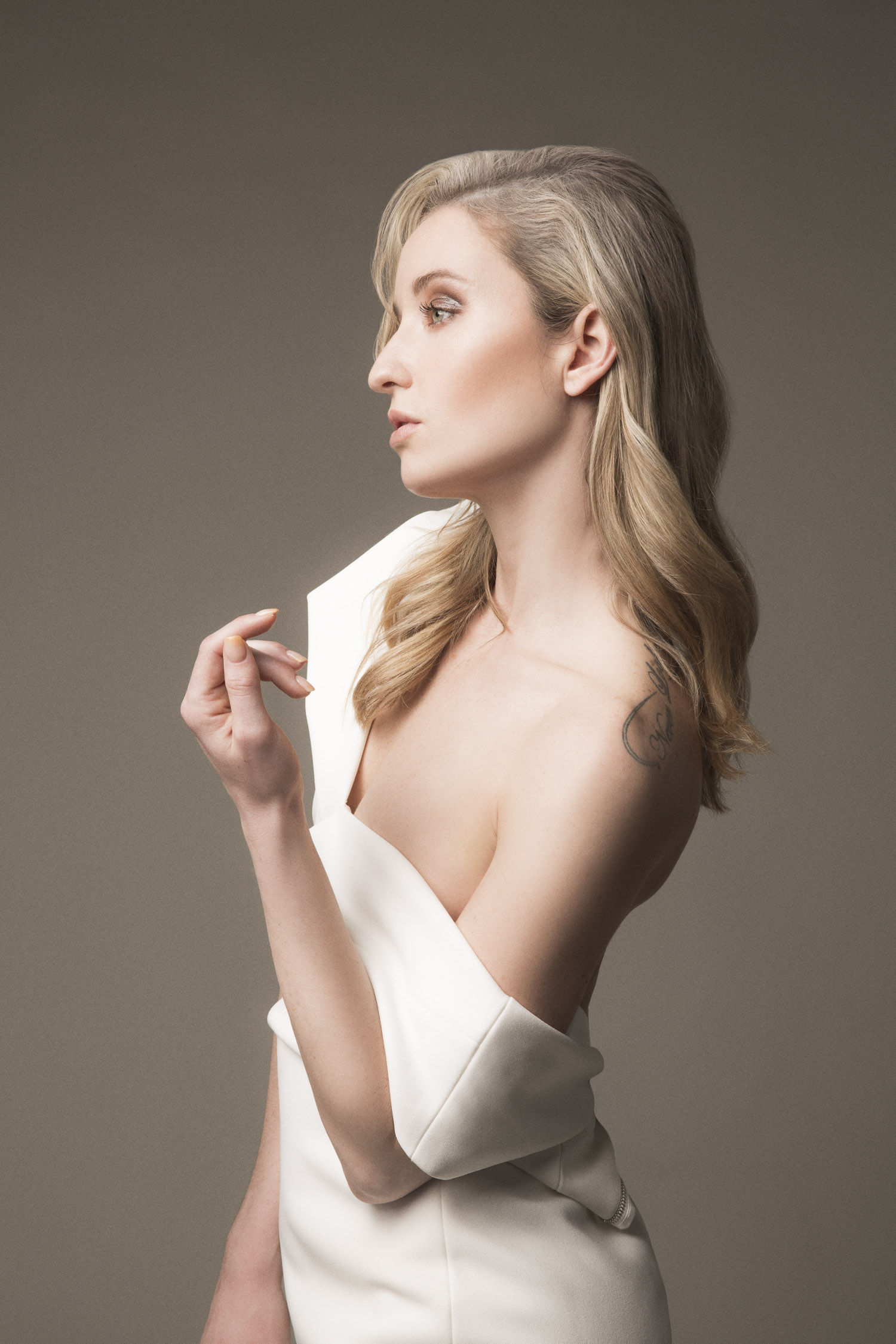 Side profile of a model wearing a white Ted Baker pencil dress