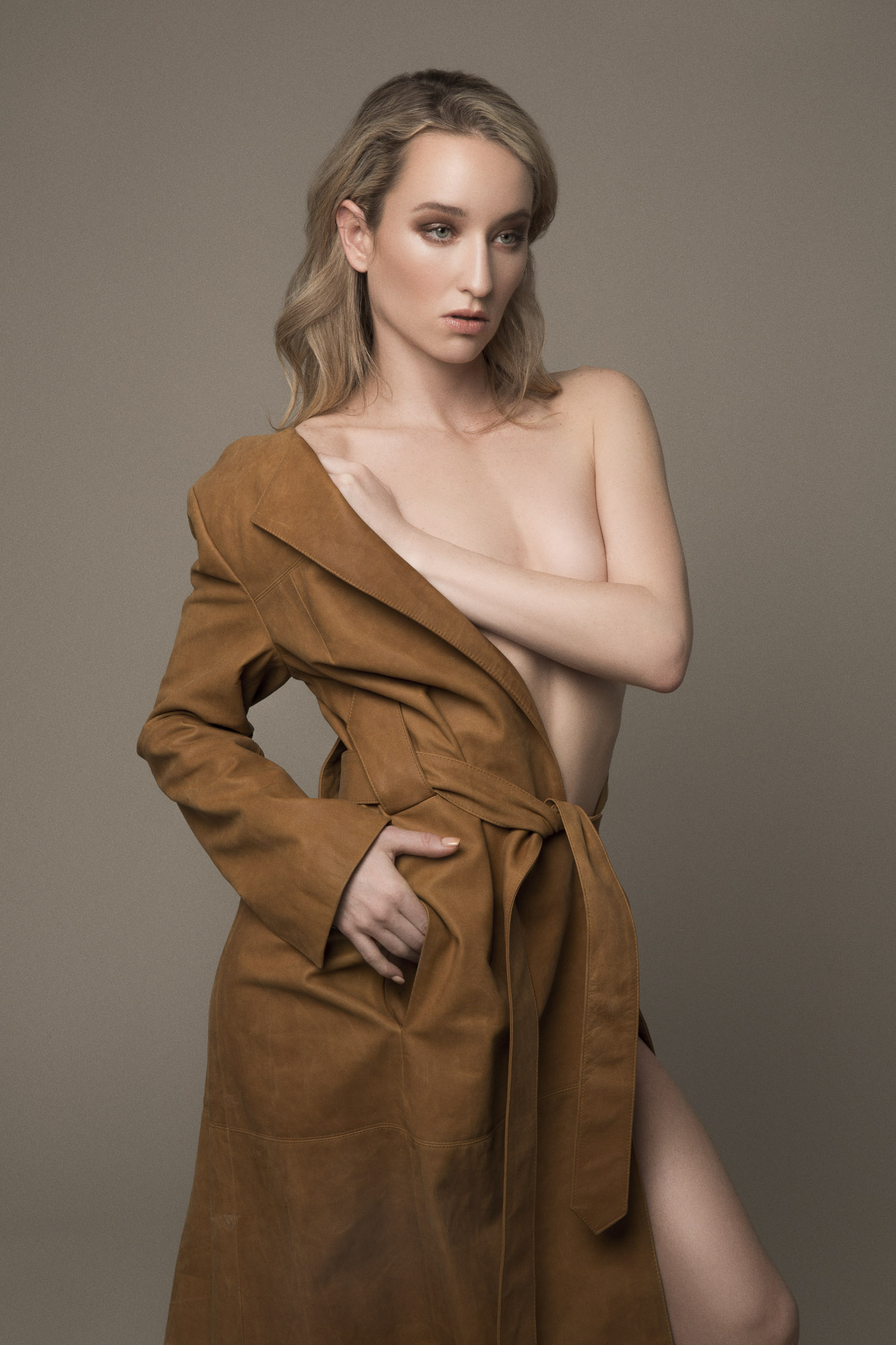 Nude model wearing a leather trenchcoat