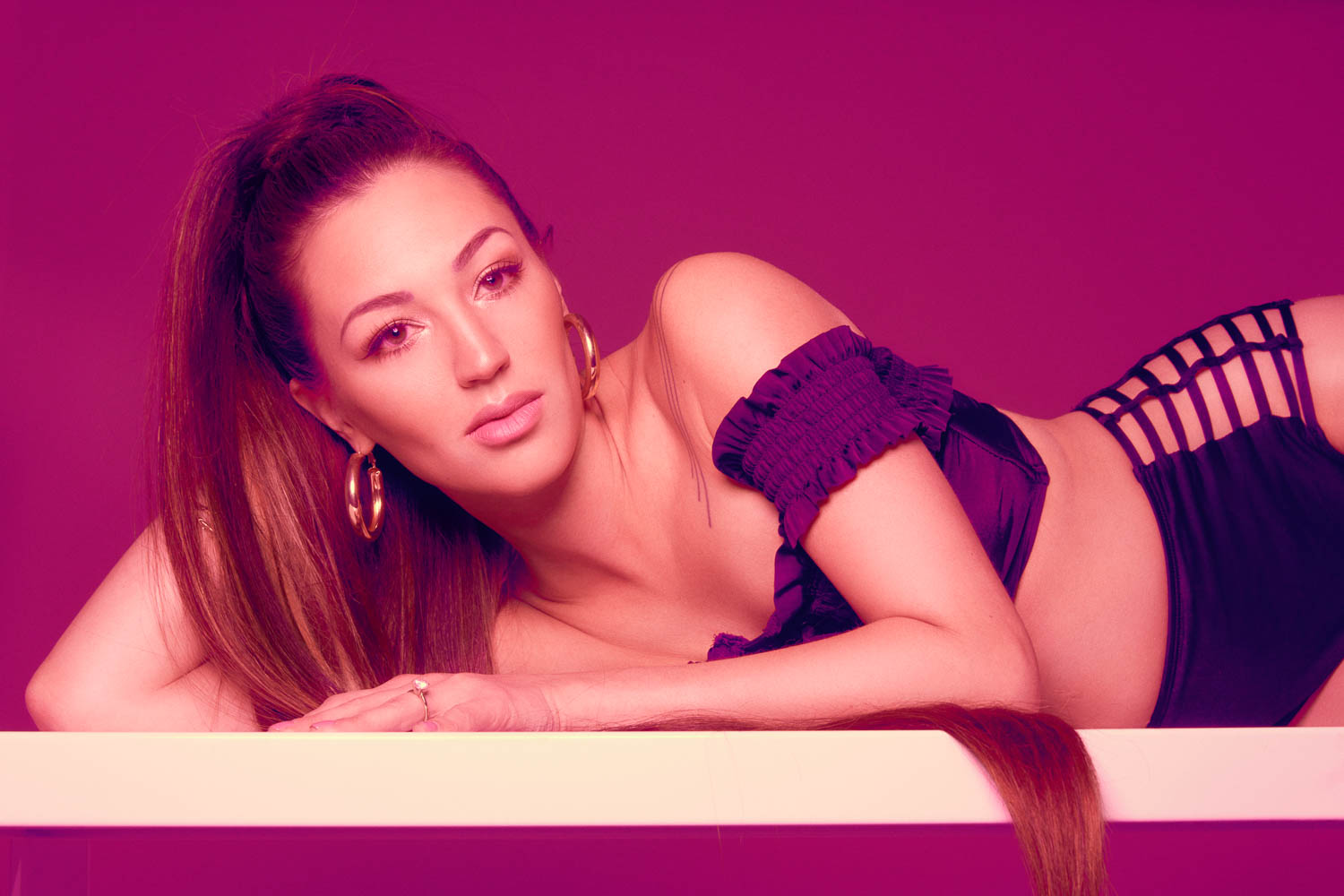 Woman laying on a white surface with pink background