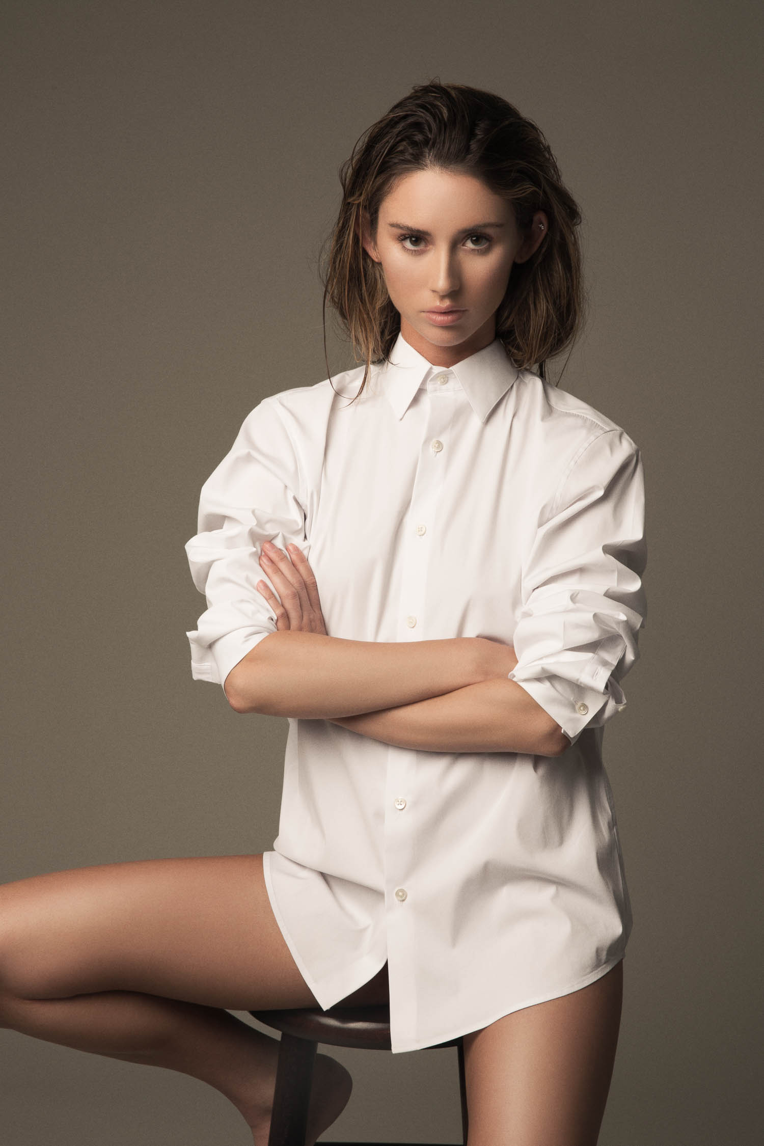 Model sitting in a white dress shirt with wet hair.