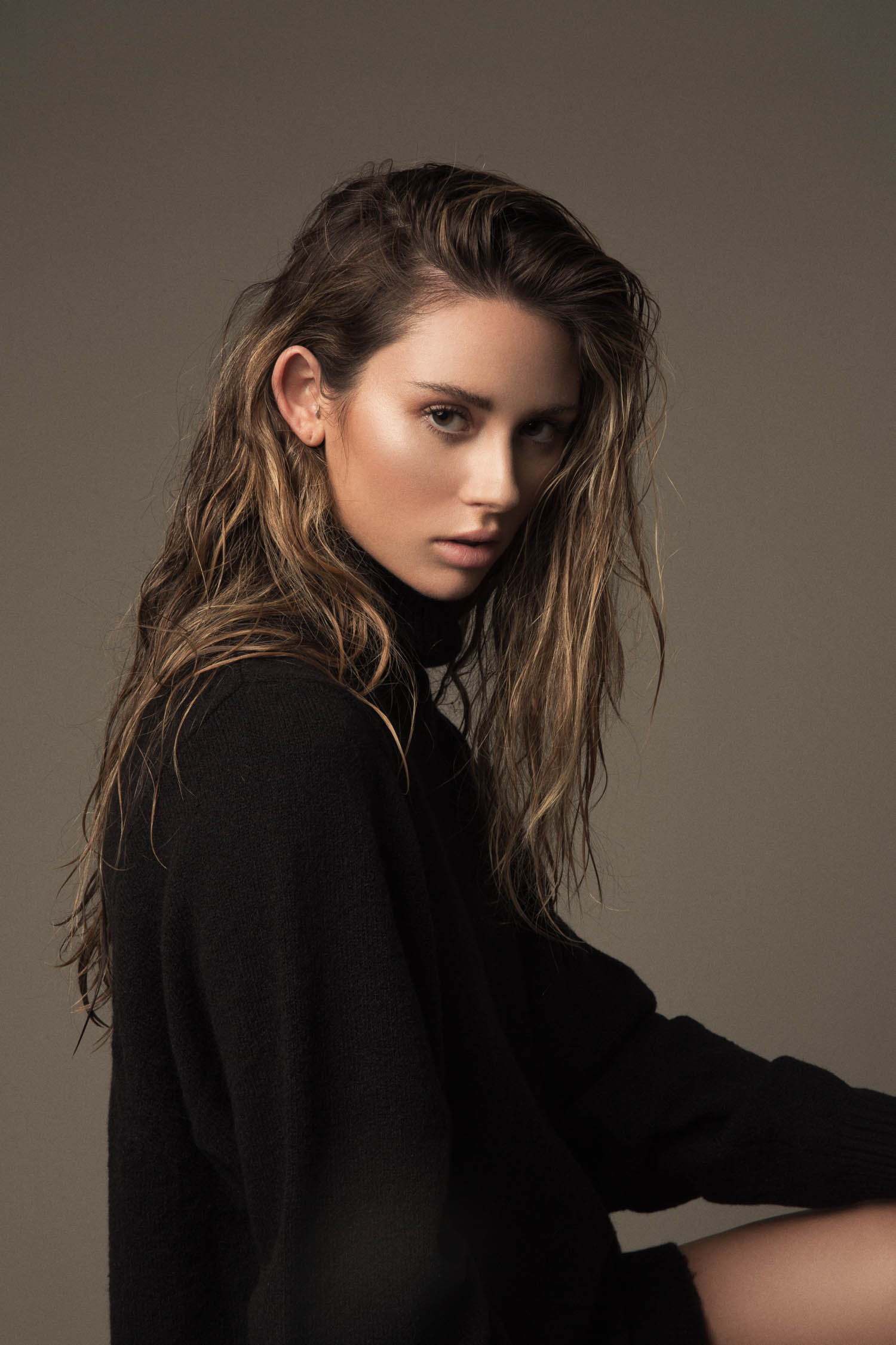 Model with wet hair wearing a black turtleneck