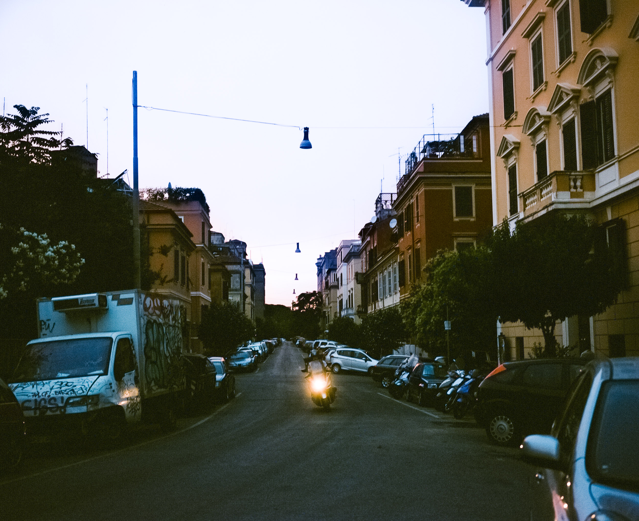 Motorcycle driving down the street in Rome with its headlight on