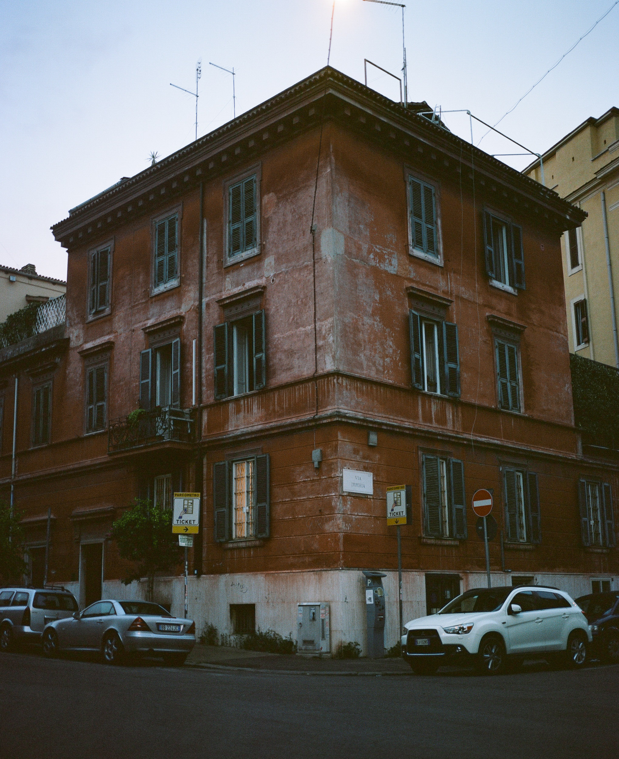 Red building in Rome, cars parked in front