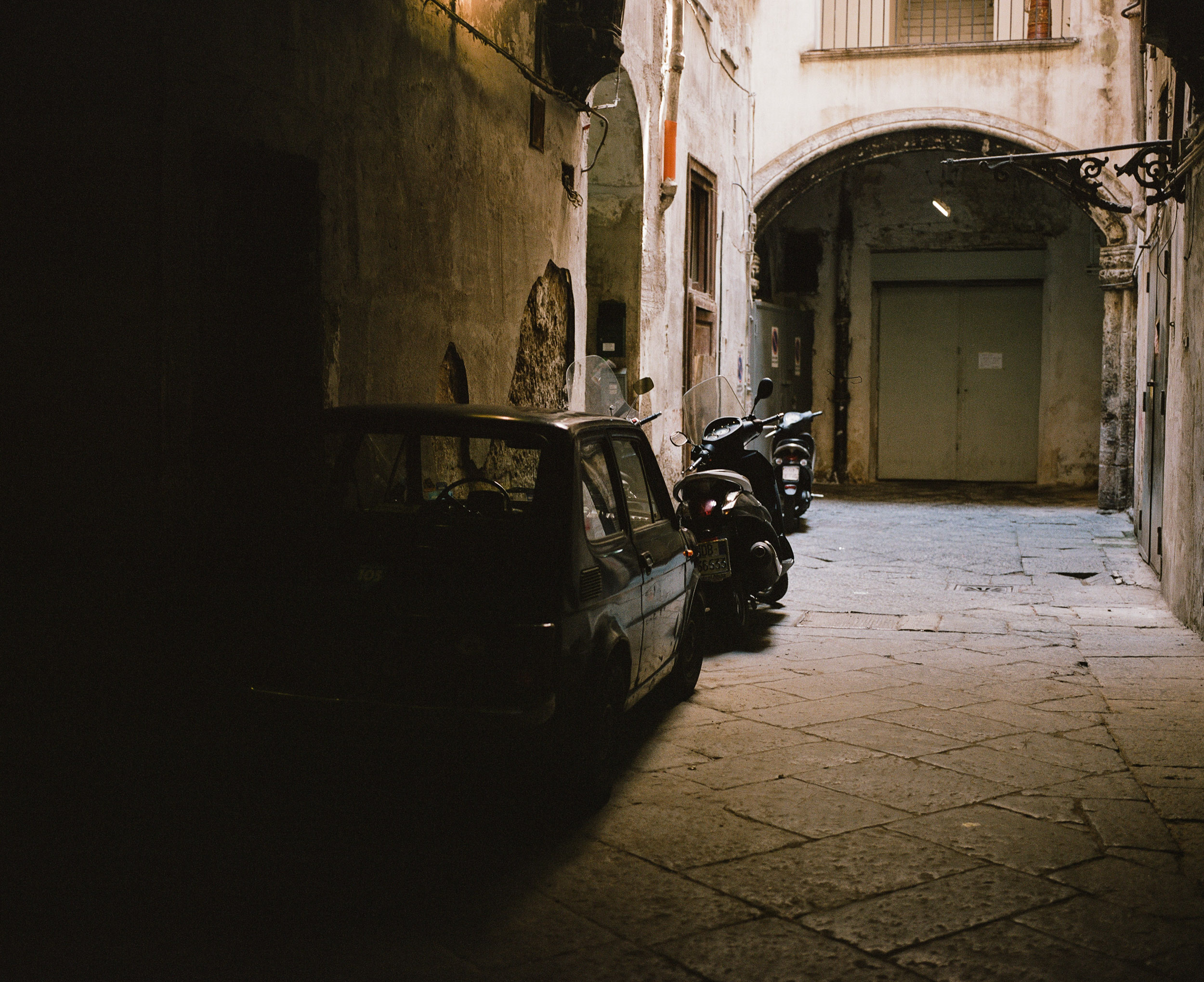 Parking courtyard in Naples, Italy with cars and scooters