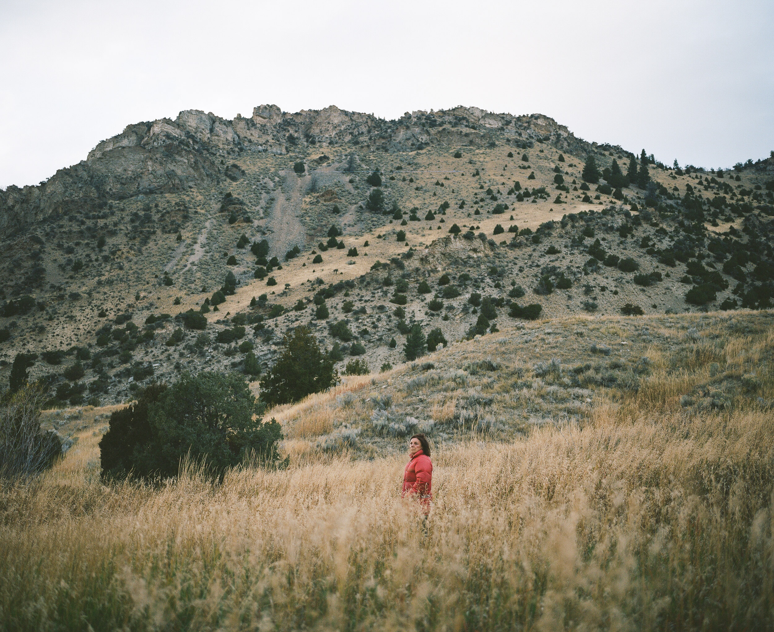Woman in a red jacket standing in a field with a Mountain behind her.