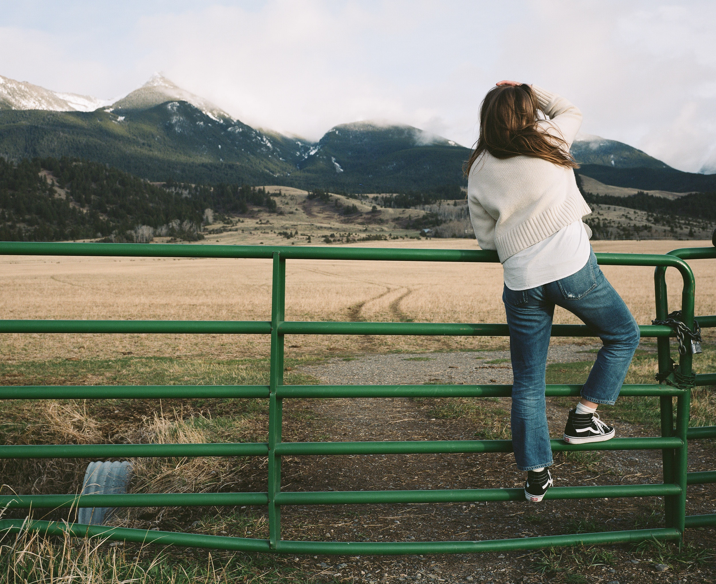 Young woman wearing jeans and a sweater standing on a green gate looking out over a field towards the mountains in Paradise Valley, Montana.