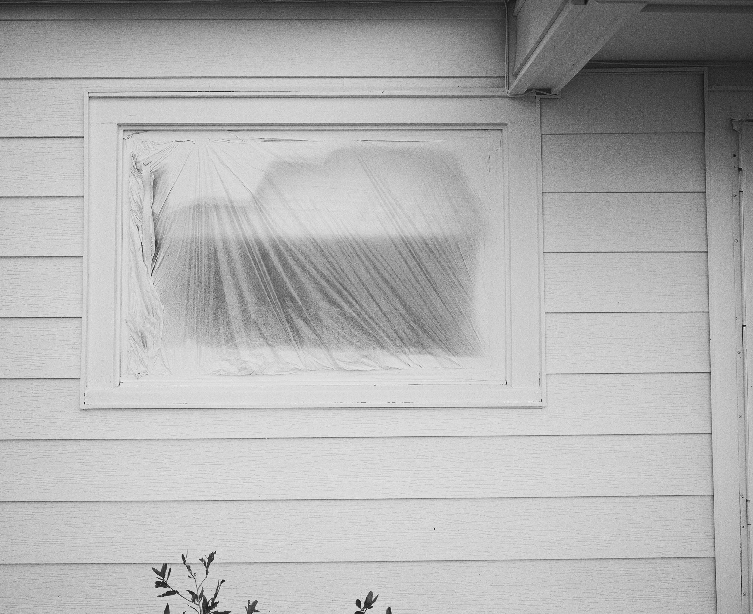 White window covered in plastic on the side of a house