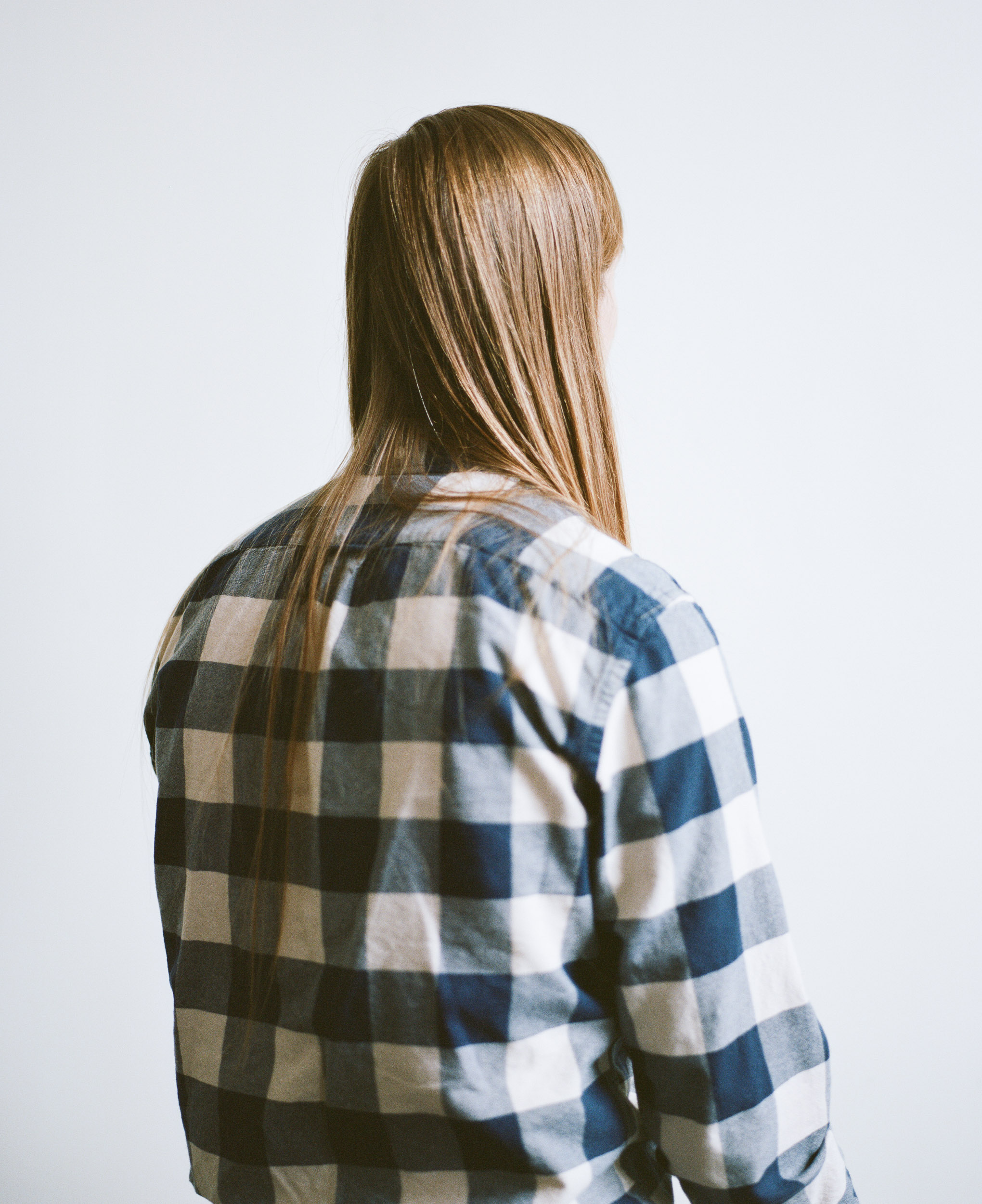 Young man with long blond hair in a blue and white plaid shirt