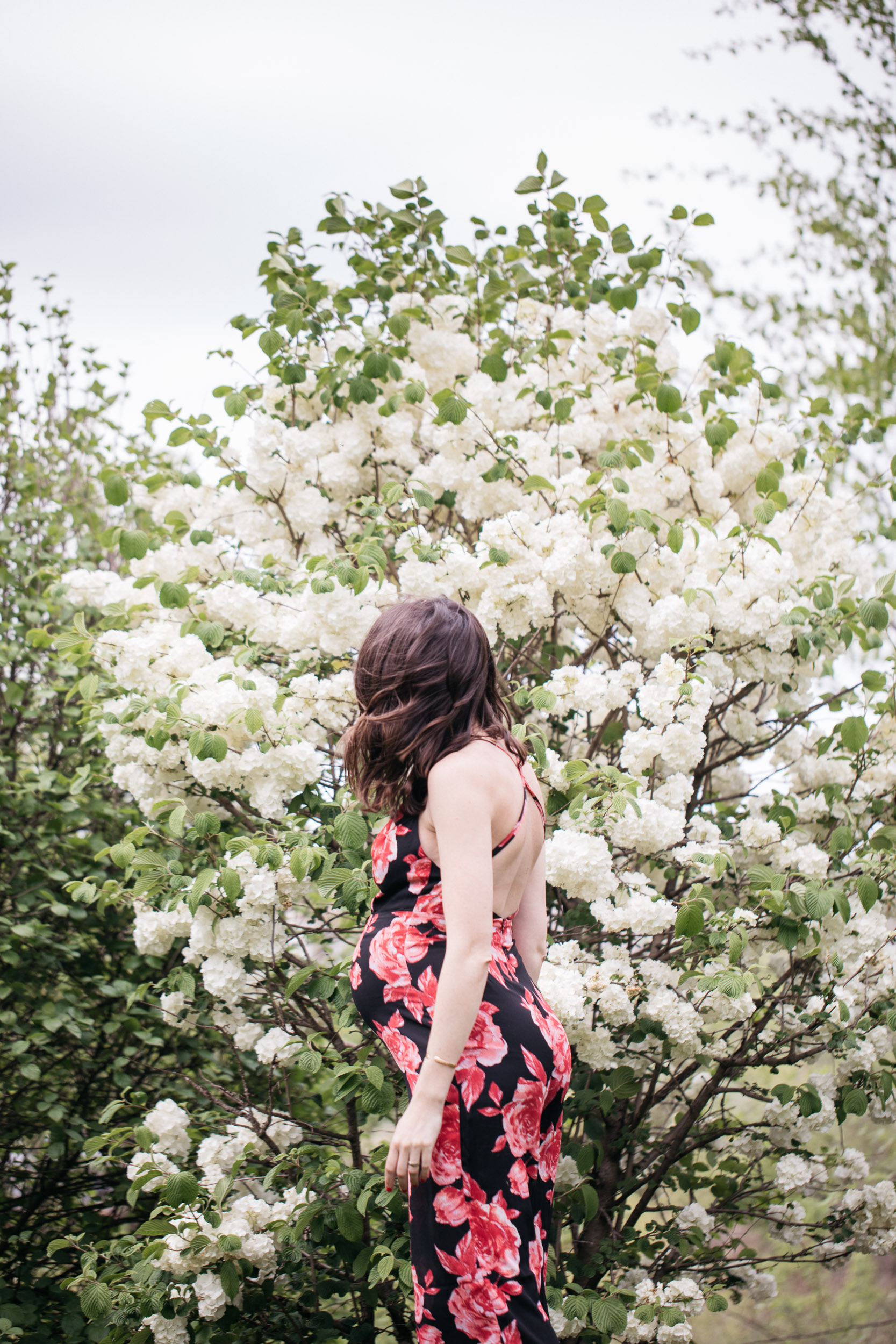 Pregnant woman in a flowered jumpsuit standing by a jasmine bush