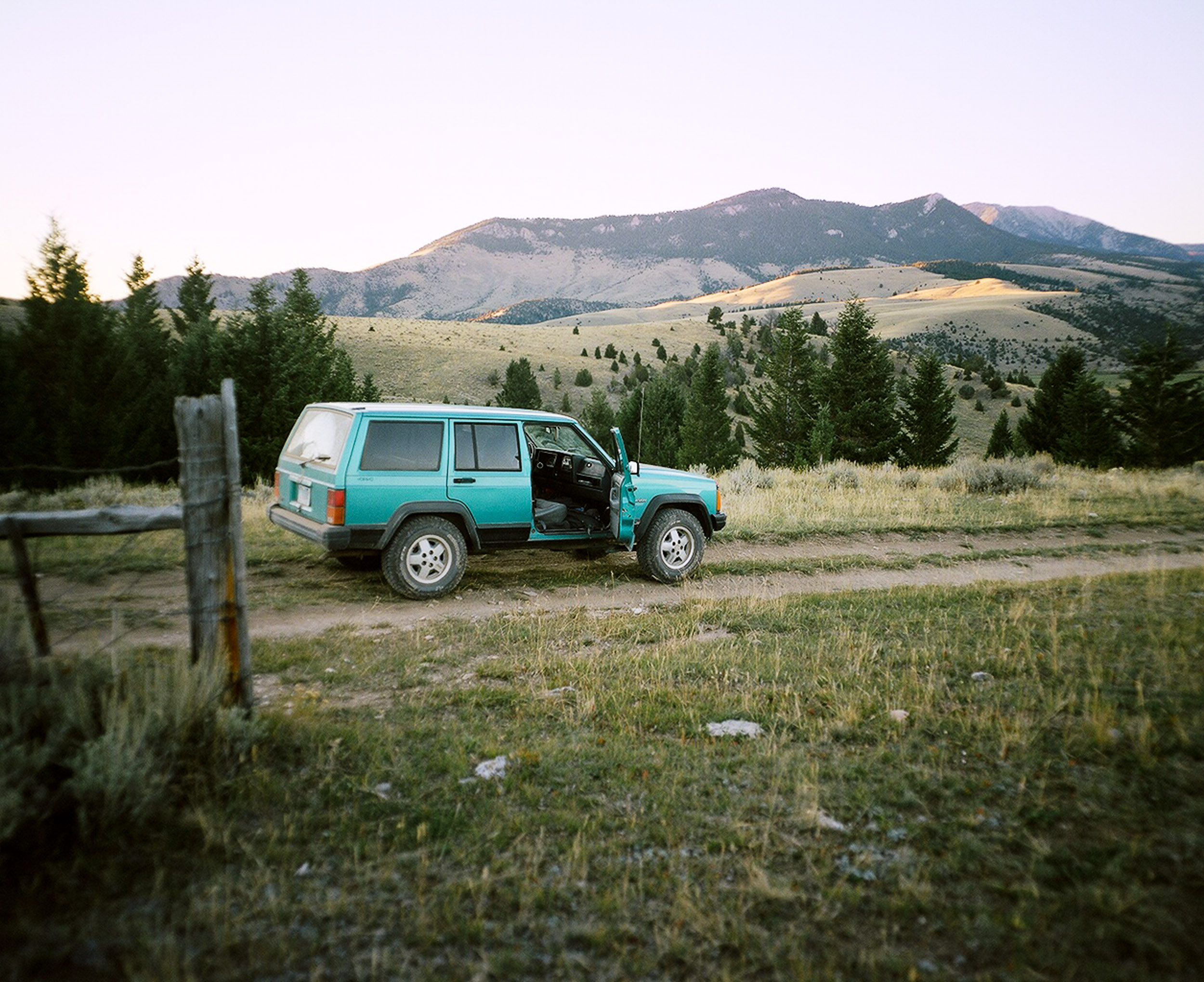 Green Jeep Cherokee with an open passenger door parked on a dirt road in Montana