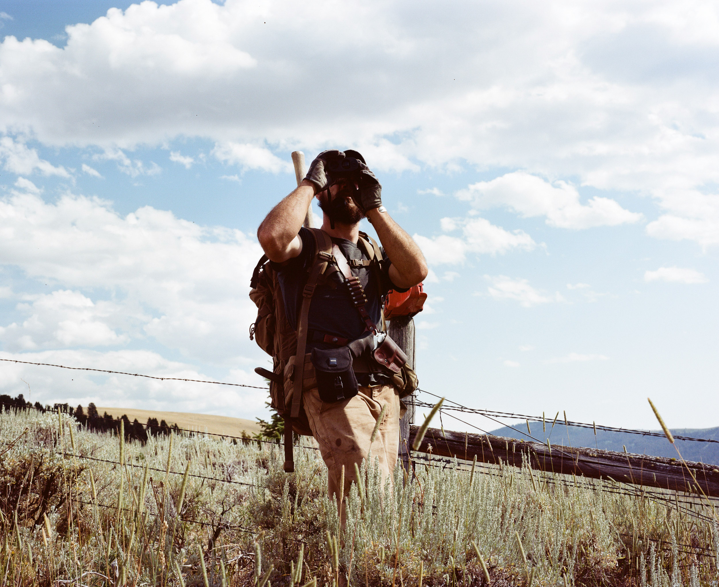 Hiker with binoculars standing in sagebrush, clouds in the background