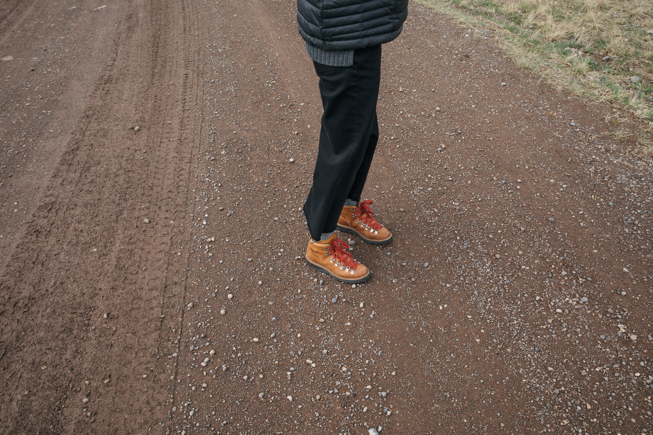 Danner boots with red laces on a woman standing on a red dirt road in Montana