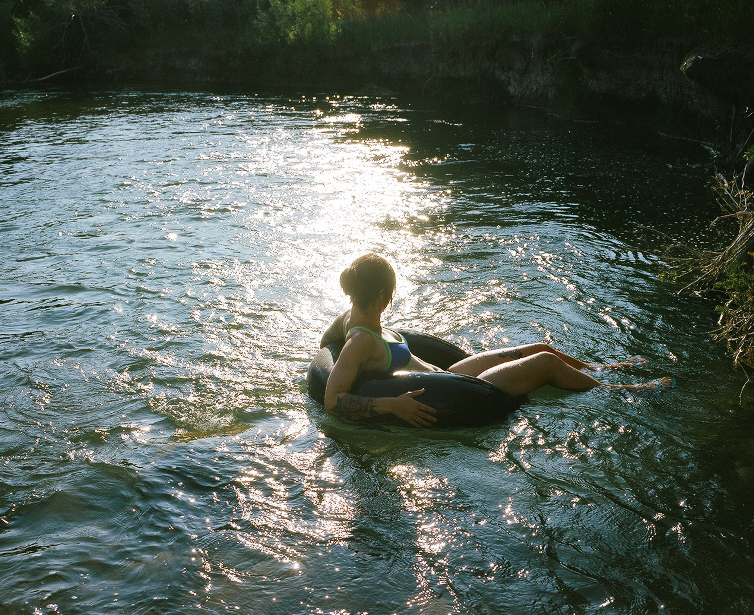 Woman floating in an innertube on a river in the glare of sunshineof