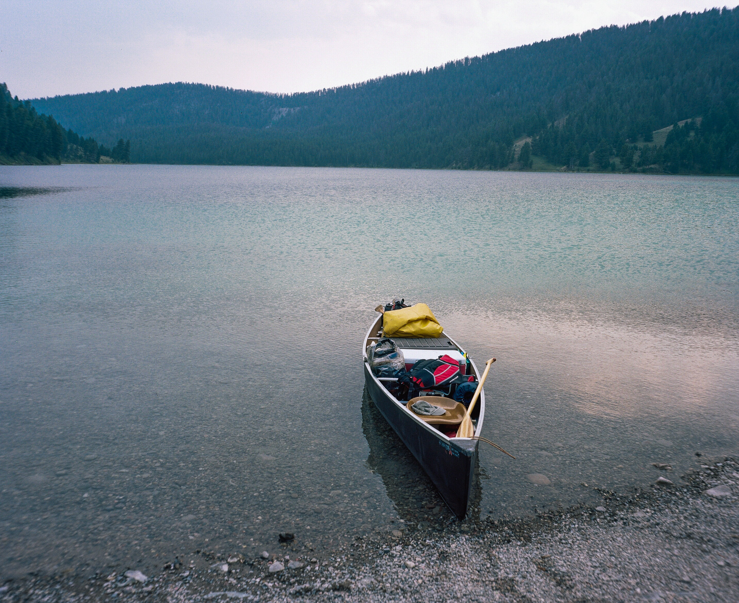 Fully loaded pack canoe in blue-green waters at Cliff Lake in Montana