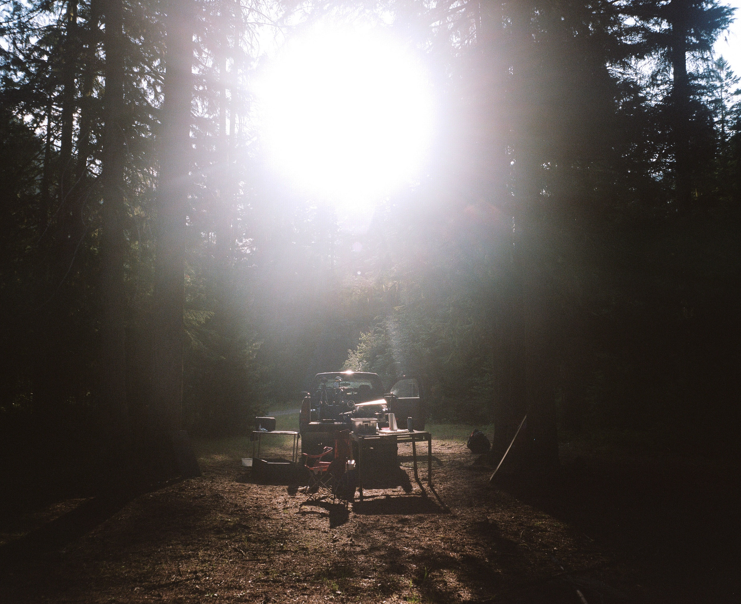 Campsite with a truck and a table and sun glare