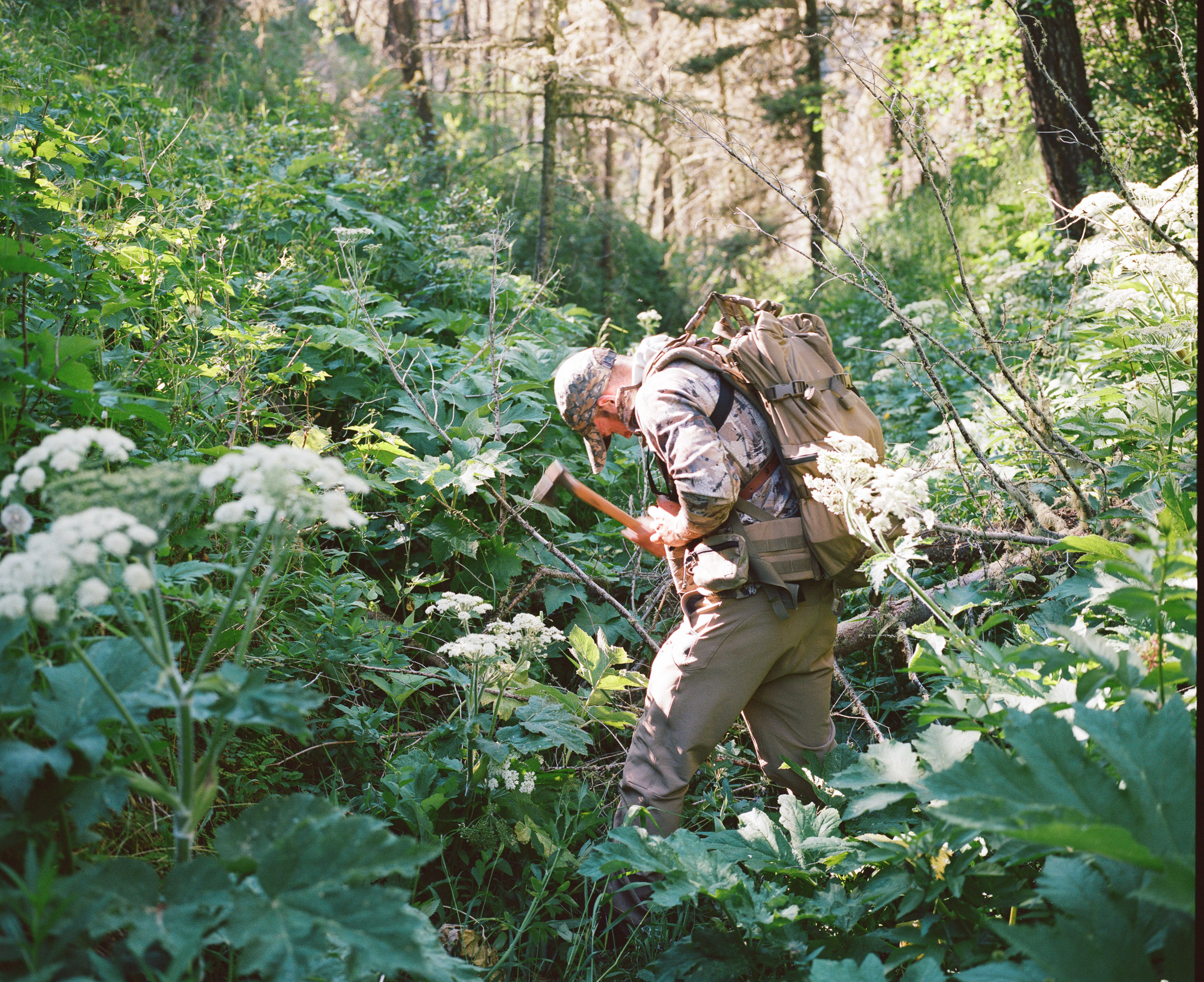 Hunter with a hatchet chopping and surrounded by grasses and flowers