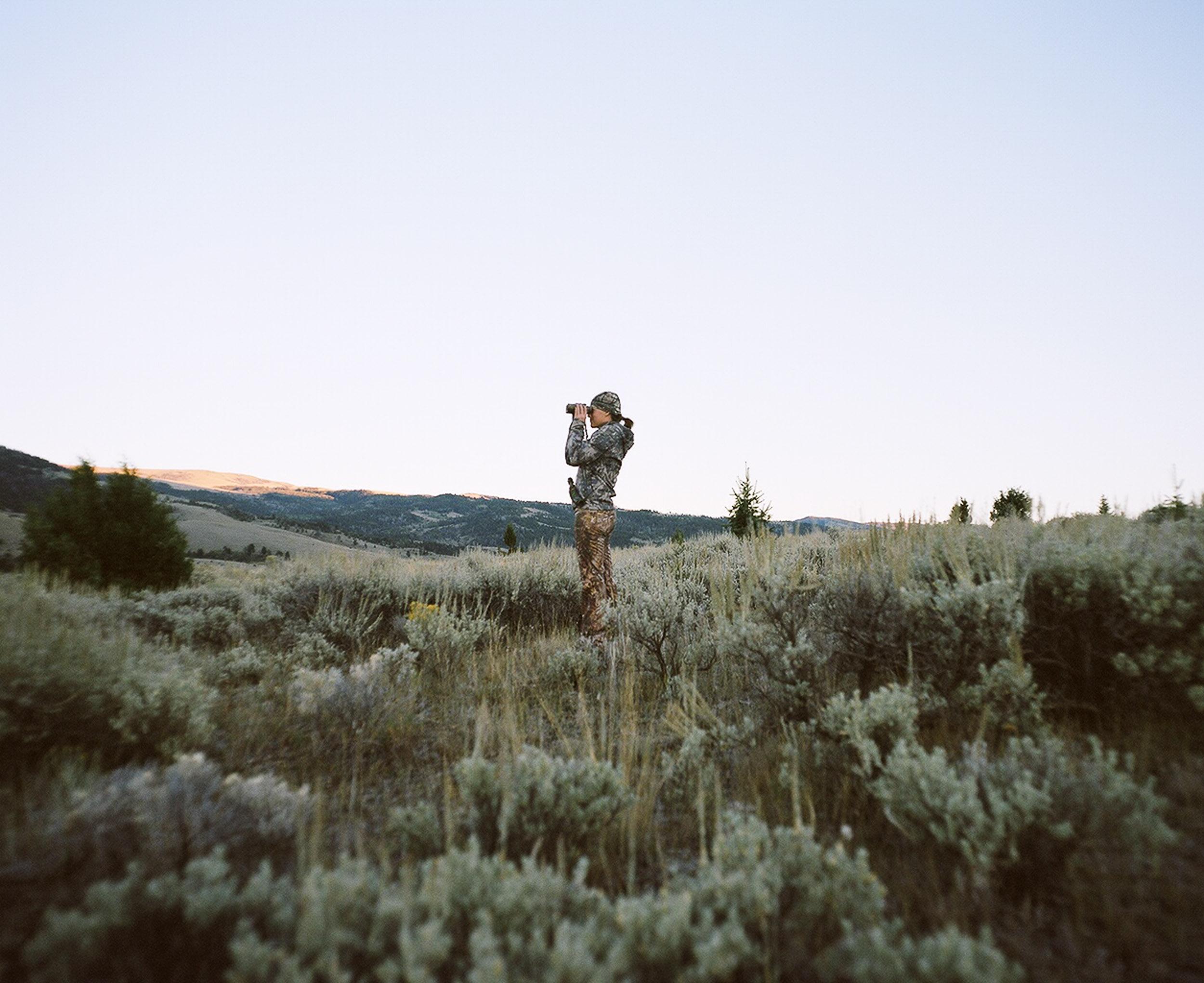 woman hunter looking through binoculars, standing in the sage brush