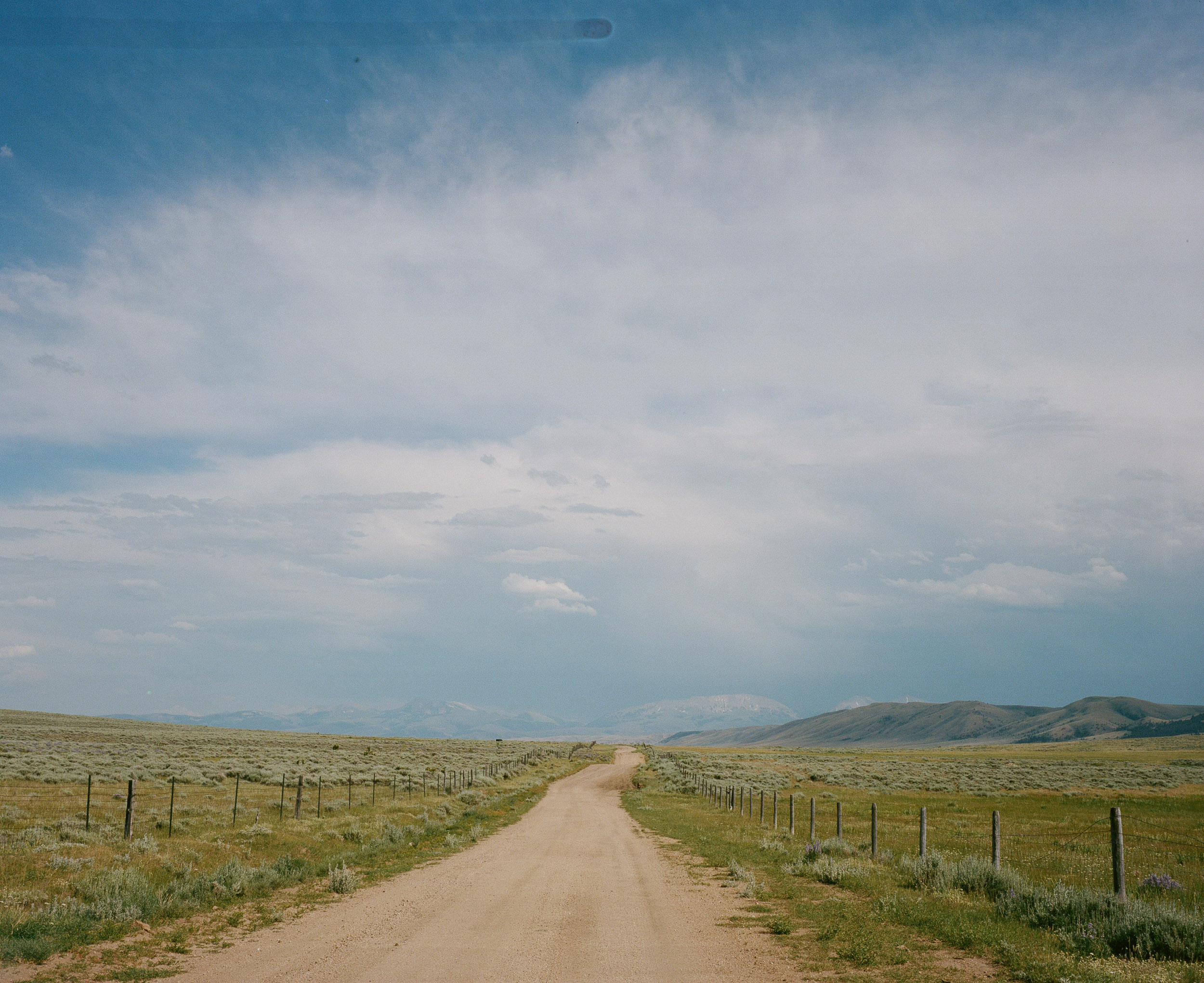 Long backroad in the country with mountains in the distance