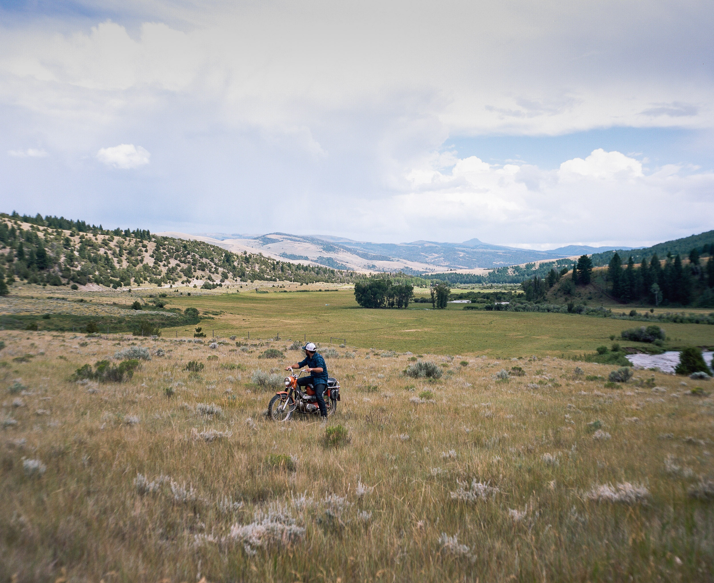 Man on a motorcycle in a field  looking out towards the mountains