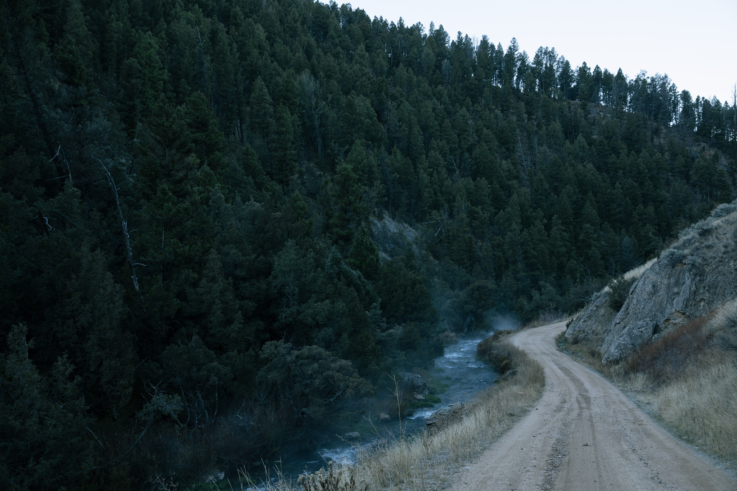 Dirtroad along a river in the mountains with mist