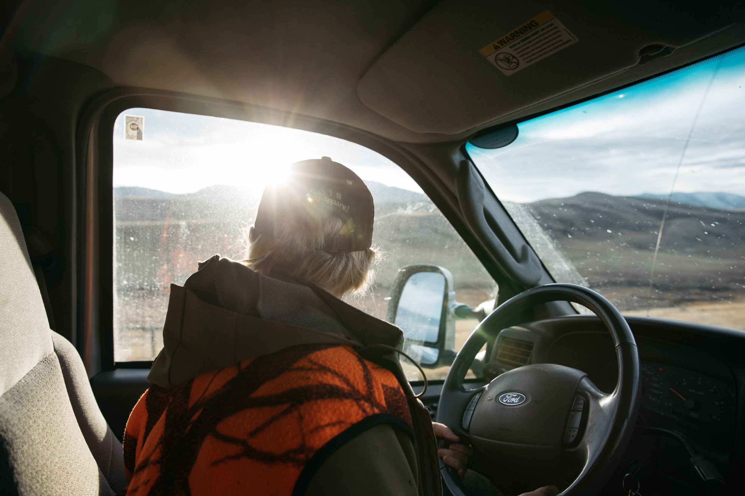 Hunter with blaze orange vest looking out of truck window
