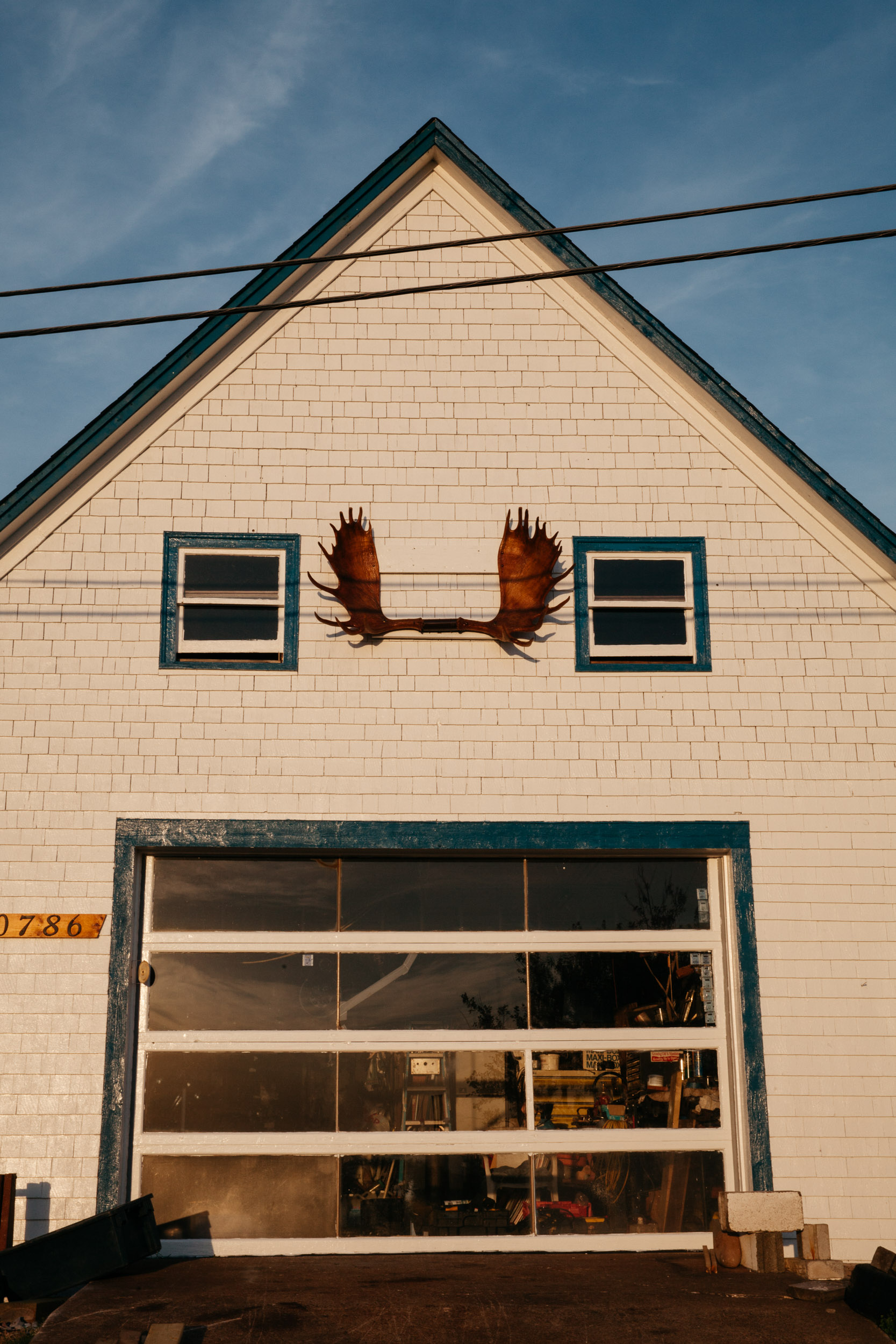 moose antlers on a garage with two windows on either side- travel photography cape breton nova scotia