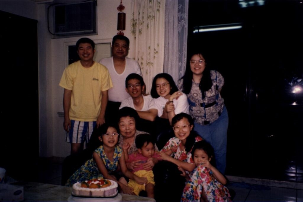 From Yi Yiing Chen: Taken on my ah ma's birthday when I was around seven.Front row from the left: me, my ah ma holding my brother, my mom and my younger sister.Back row from the left: my dad, my uncle and three of his children