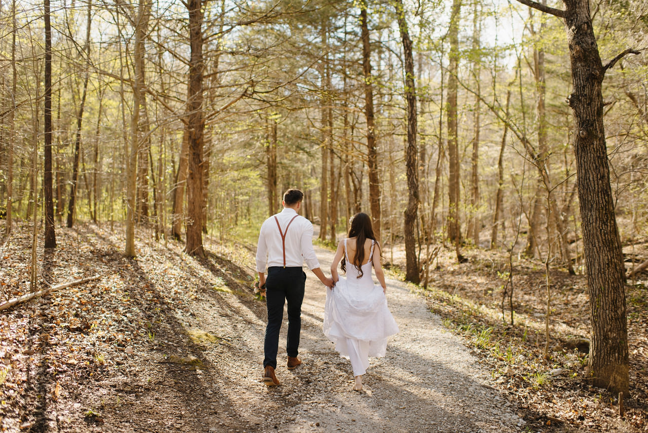 A bride and groom walk through the woods by the Buffalo River with Arkansas Adventure Destination Photographer Colby and Jess