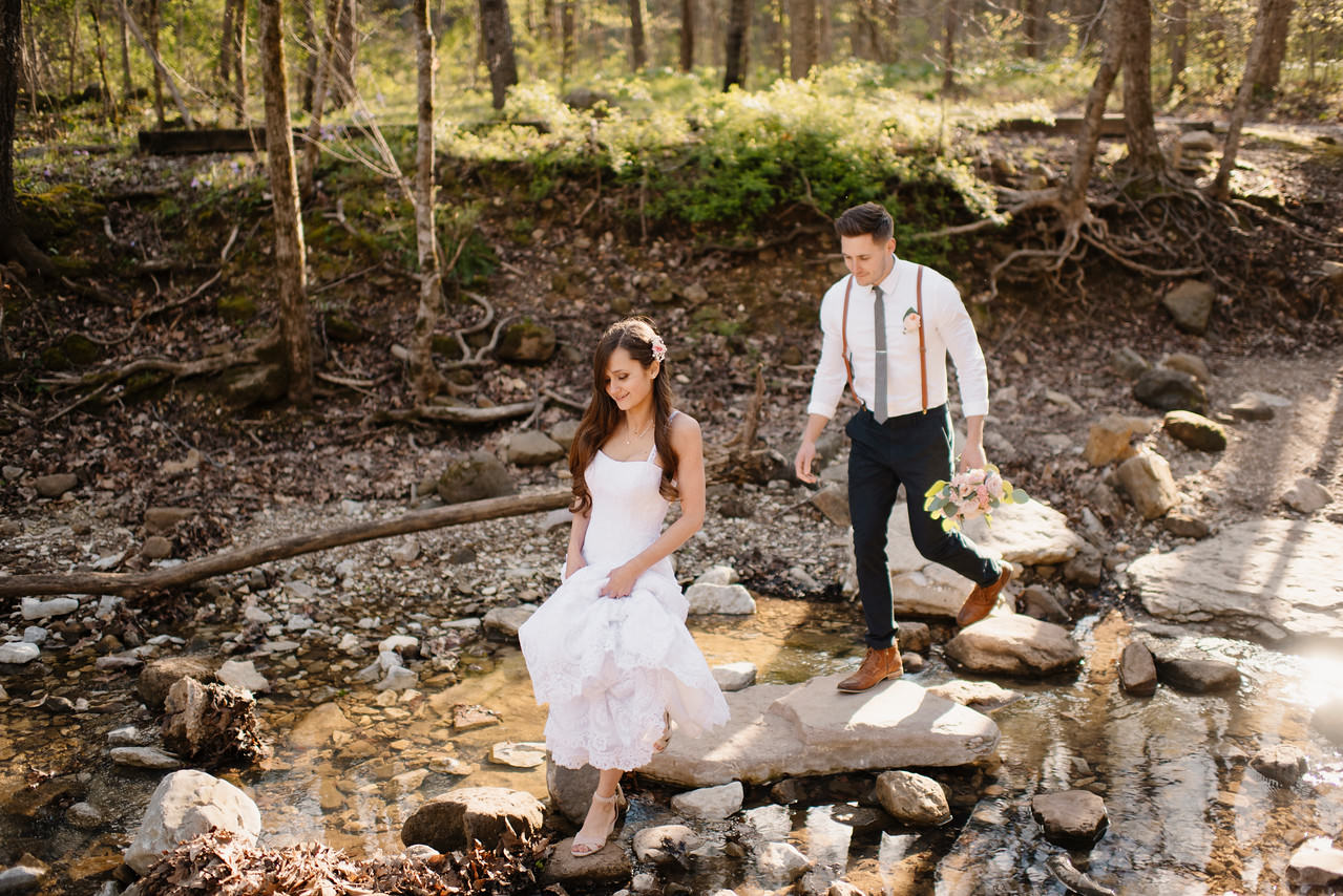 An adventurous bride and groom cross a creek before their Buffalo River Wedding by Arkansas Destination Photographer Colby and Jess