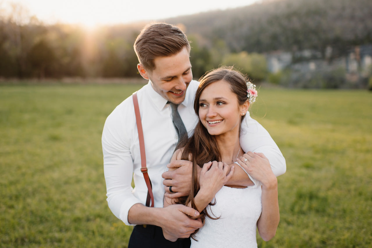 A groom holds his bride close after their Steele Creek Wedding at the Buffalo River with Arkansas Adventure Destination Photographer Colby and Jess