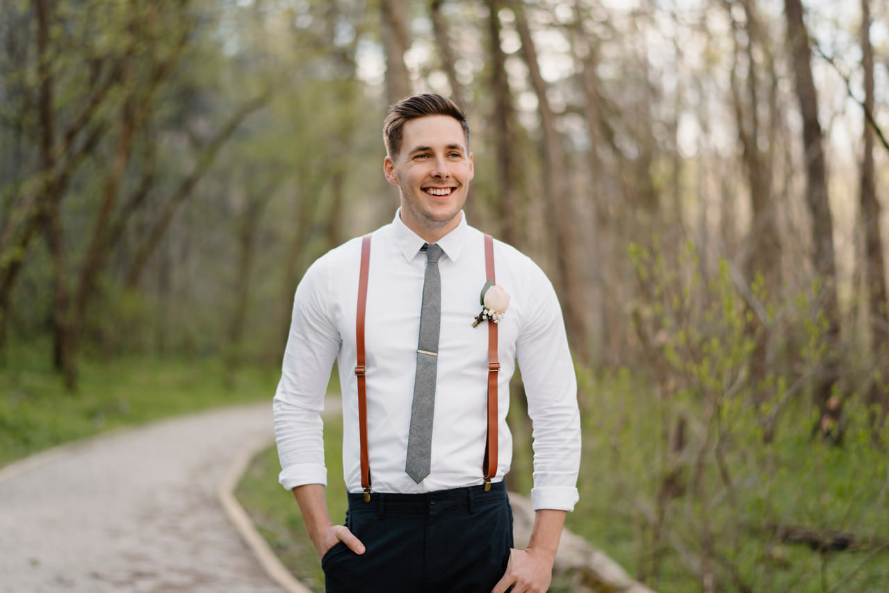 A groom stands in the woods before his Buffalo River Wedding with Arkansas Adventure Destination Photographer Colby and Jess