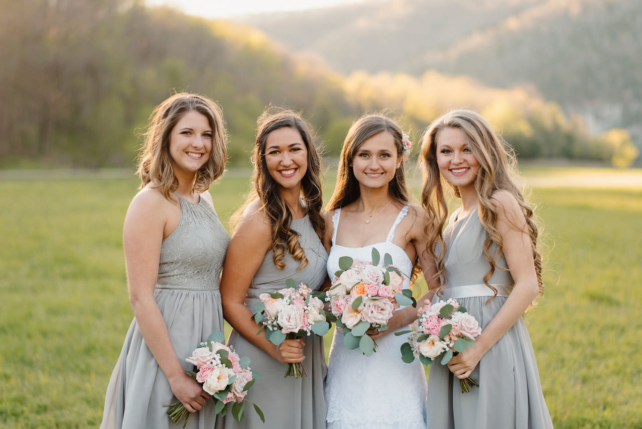 A bride and her bridesmaids stand in the open field by the Buffalo River after her wedding by Arkansas Adventure Destination Photographer Colby and Jess