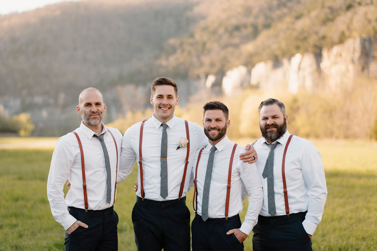 A groom stands with his groomsmen after his Steele Creek Buffalo River Wedding with Arkansas Adventure Destination Photographer Colby and Jess