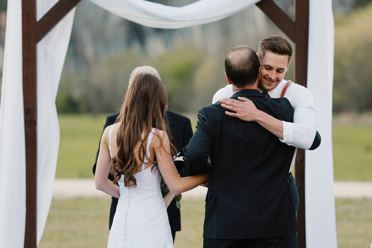 The father of the bride hugs the groom as he gives away his daughter during a Buffalo River Wedding with Arkansas Adventure Destination Elopement Photographers Colby and Jess