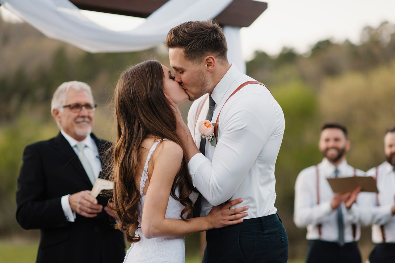 A bride and groom kiss during their Buffalo River Wedding by Arkansas Adventure Destination Photographer Colby and Jess
