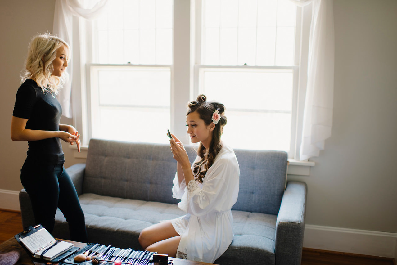 A makeup artist prepares a bride for her Ozarks wedding by Buffalo River Elopement Photographers colby and jess