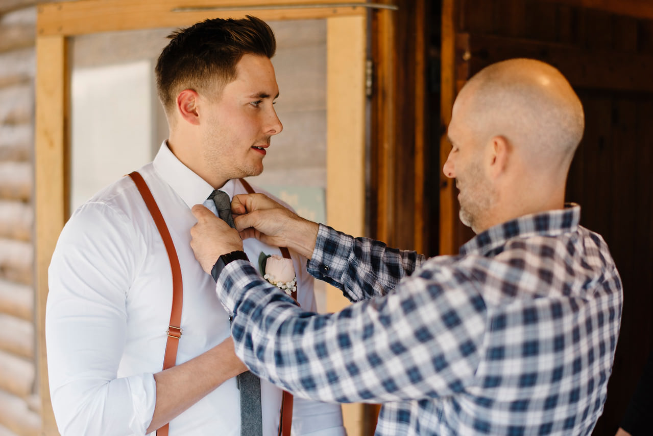 A groom's brother straightens his tie before his Outdoor Buffalo River Wedding by Ozarks Adventure Destination Elopement Photographers Colby and Jess