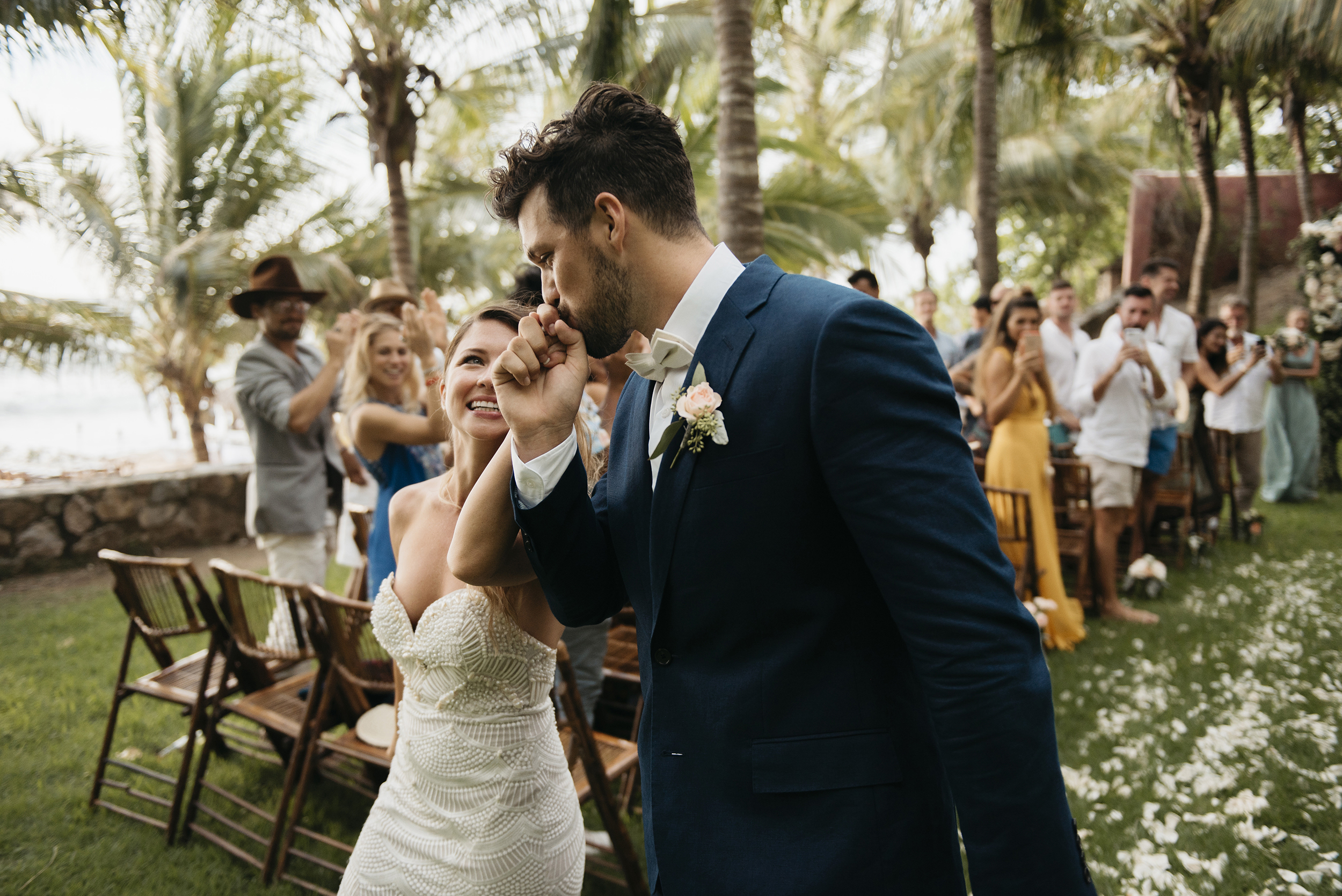 Groom kisses his brides hand as they walk down the aisle during Sayulita Wedding by Puerto Vallarta Elopement photographer Colby and Jess colbyandjess.com