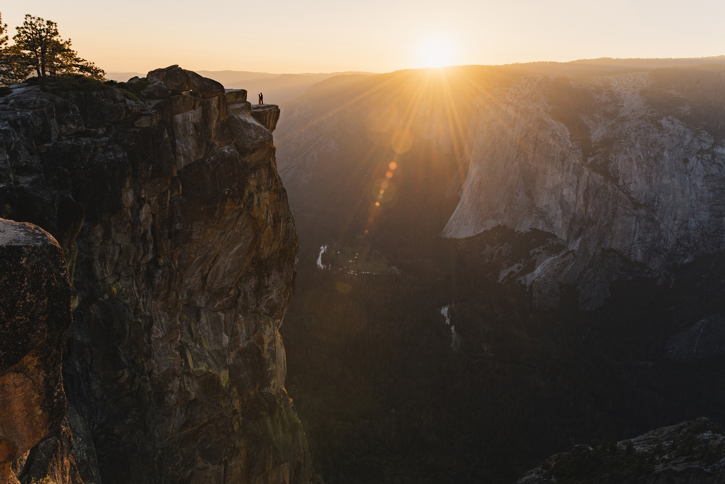 Sunset at Taft Point with couple on cliff edge during adventure engagement photography session by Yosemite Elopement Photographer Colby and Jess colbyandjess.com