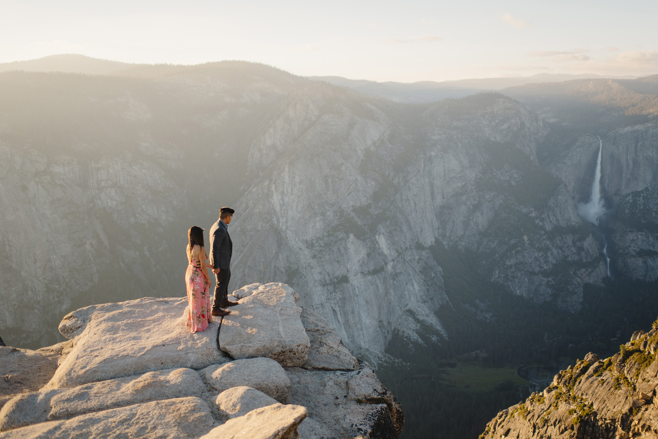 Daring couple look down on Yosemite Valley during engagement photography by Yosemite Wedding Photographer Colby and Jess  colbyandjess.com