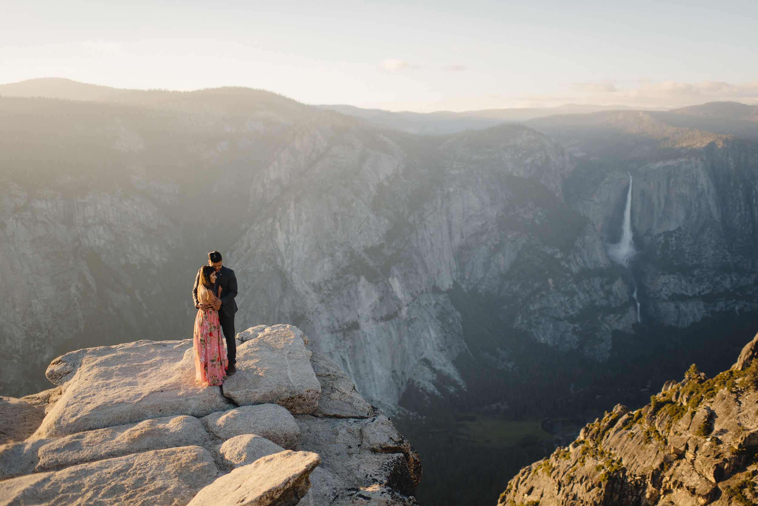 Adventurous couple snuggle on edge of Taft Point overlooking Yosemite Falls during engagement photography by Yosemite Wedding Photographers Colby and Jess colbyandjess.com