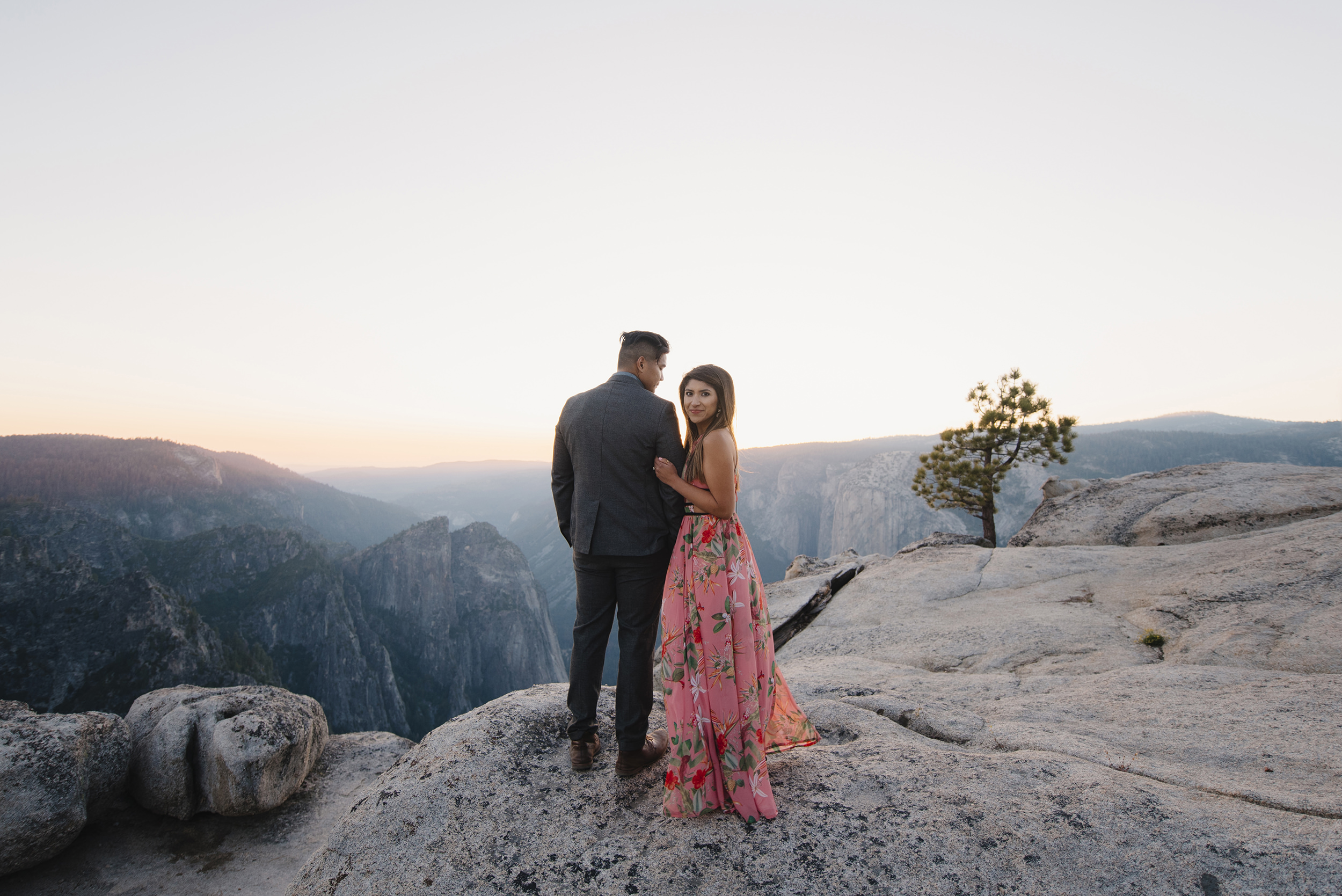 She glances back over her shoulder as they watch the sunset from Taft Point during engagement photography by Yosemite Wedding Photographers Colby and Jess colbyandjess.com