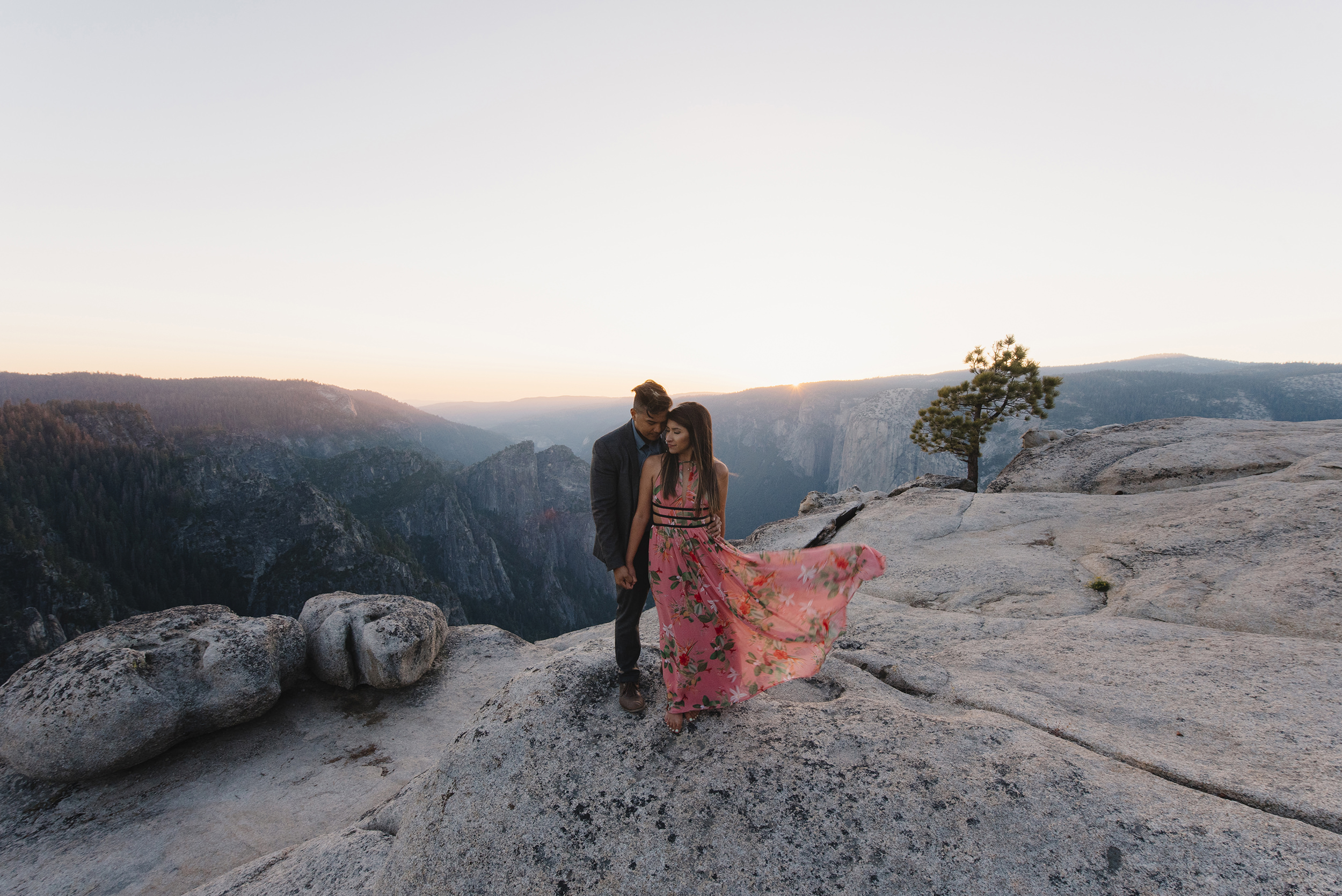 Bride to be's dress blows in the wind at sunset during their Taft Point Adventure photography session by Yosemite Wedding Photographers Colby and Jess colbyandjess.com