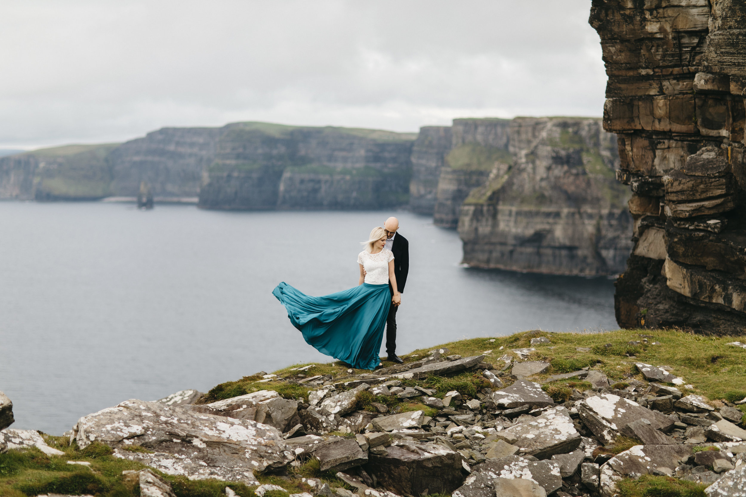 Married couple stands on edge of Cliffs of Moher by Adventurous Ireland Elopement Photographer Colby and Jess