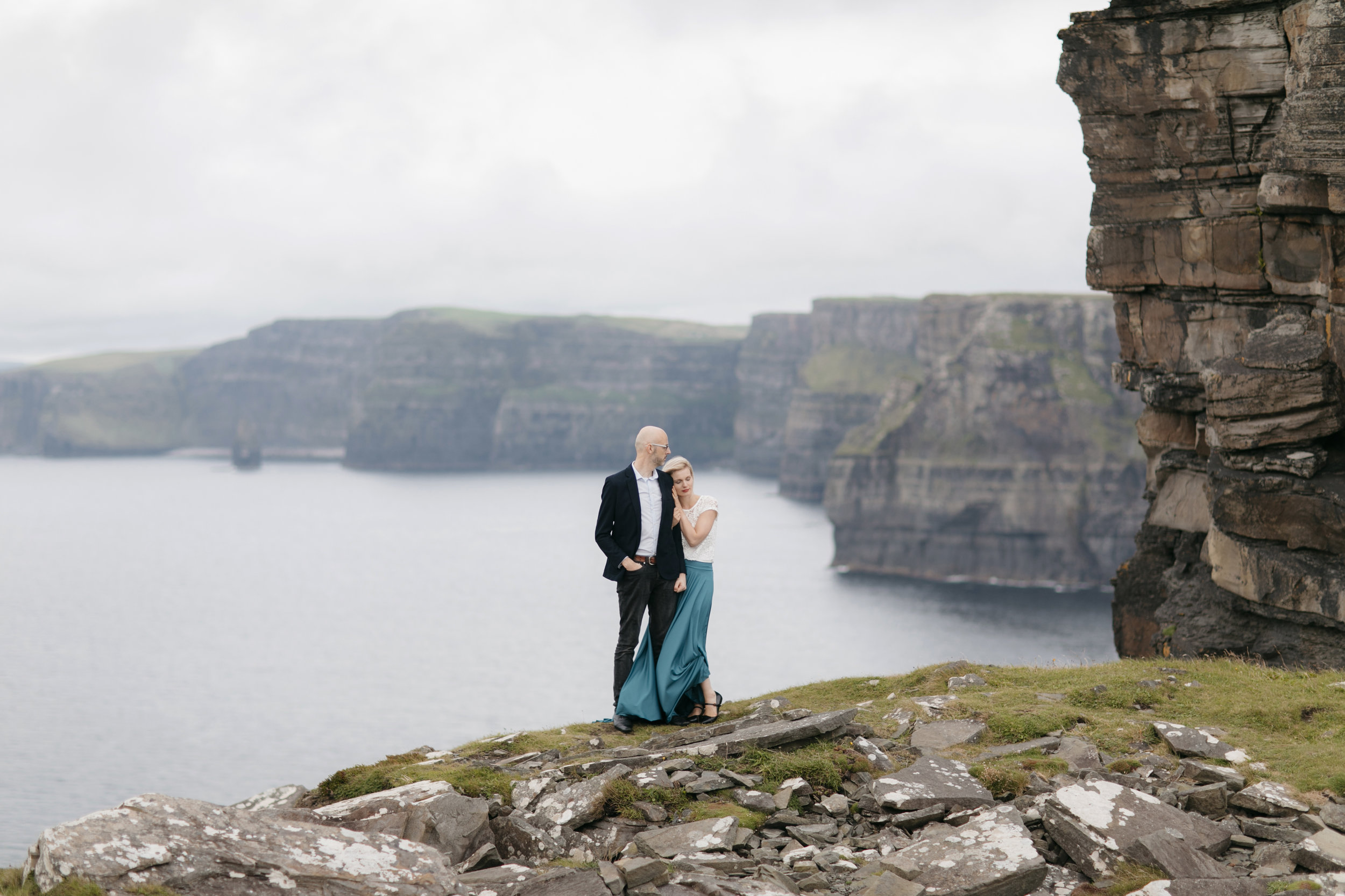 Lovely couple snuggle up at Cliffs of Moher during adventure photography session by Ireland elopement photographer Colby and Jess