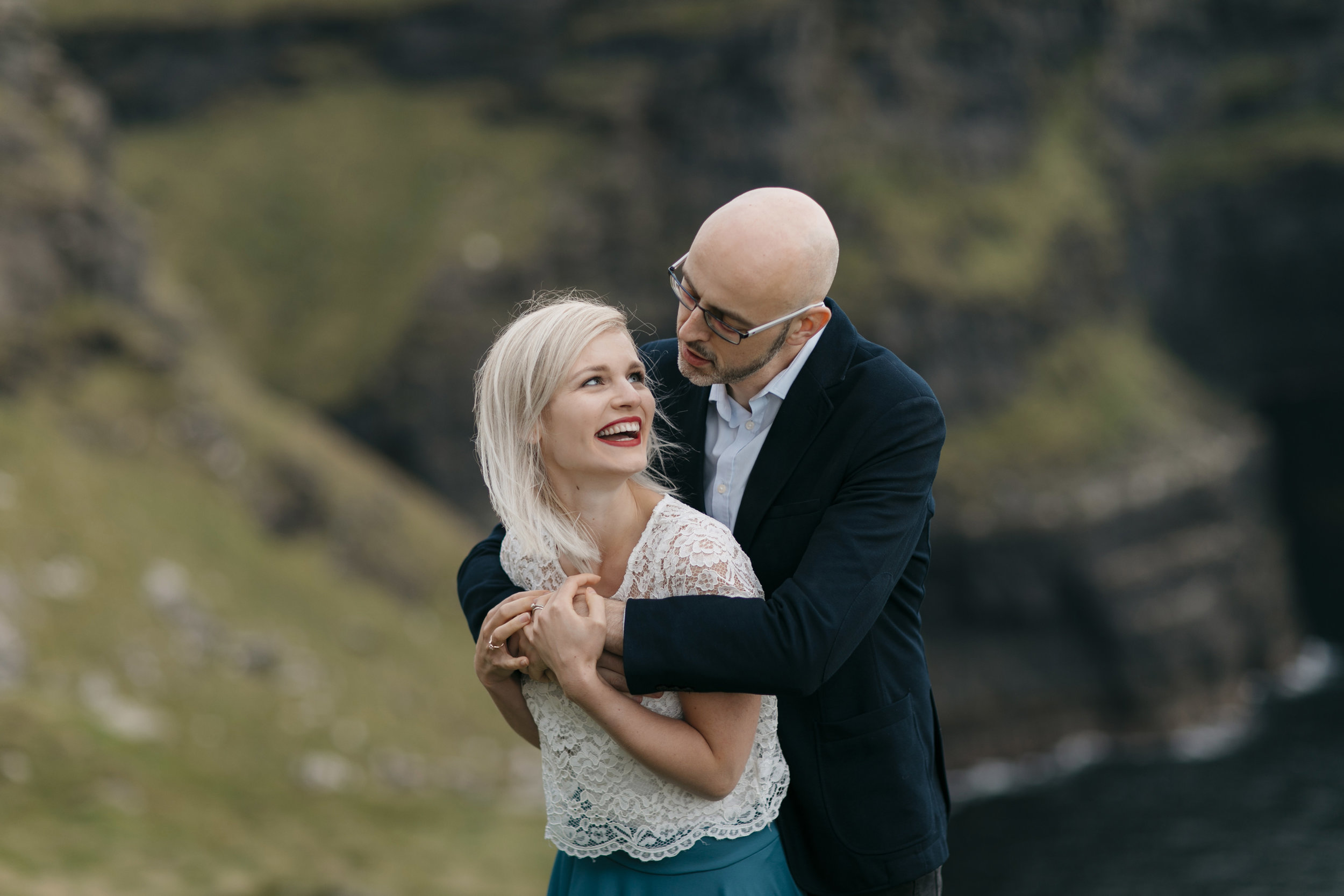 Adorable couple laugh while being photographed at Cliffs of Moher by Adventure Wedding Photographer Colby and Jess