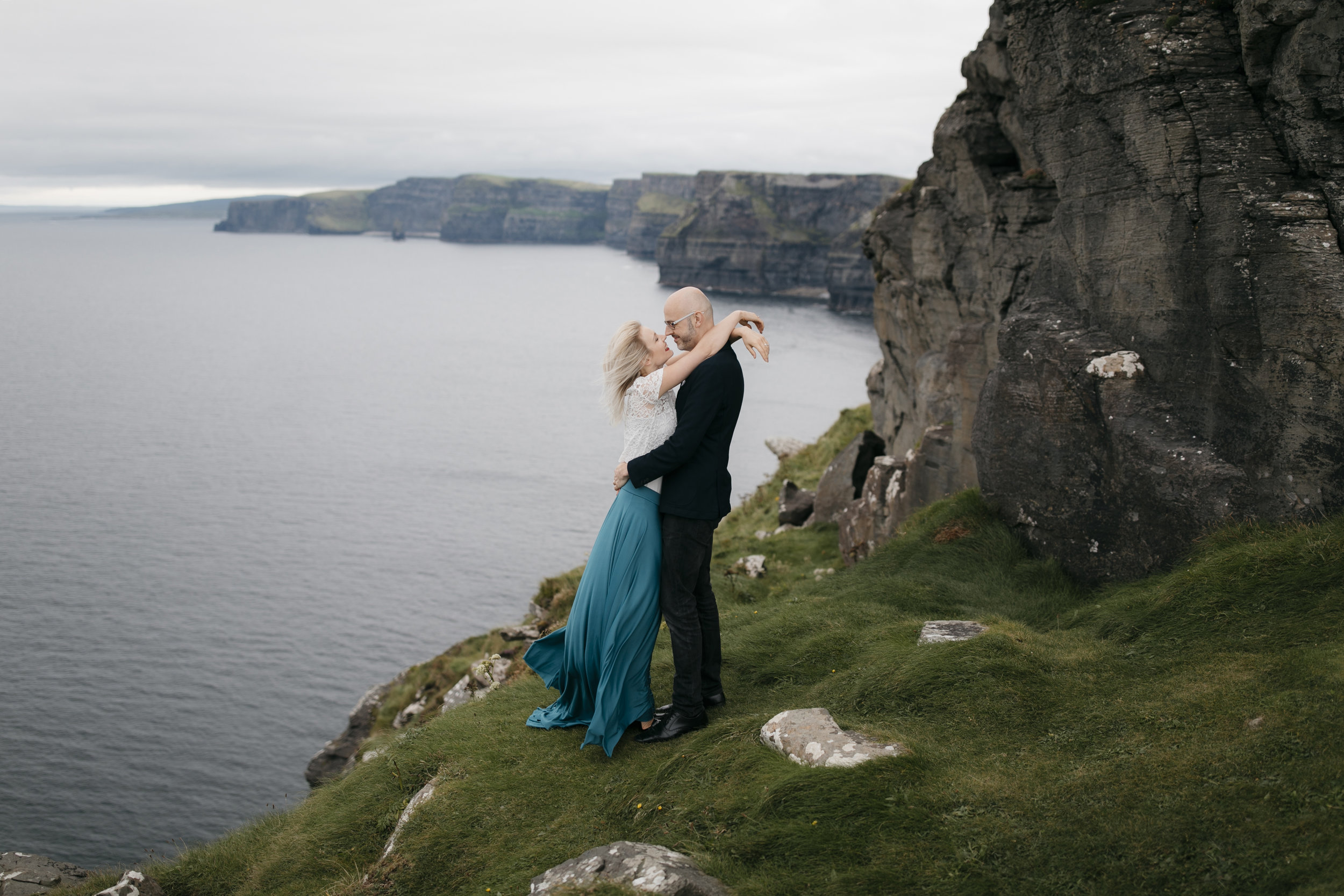 Adventurous couple cherishing each other at the Cliffs of Moher by Ireland Elopement Photographer Colby and Jess