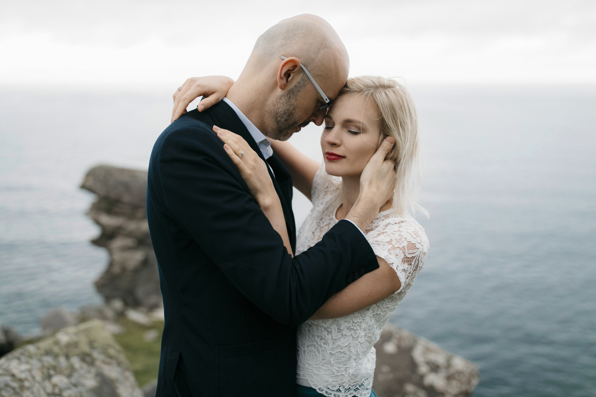 A man taking his wife closely in his arms during Cliffs of Moher Adventure Photography Session by Ireland Elopement Photographer Colby and Jess